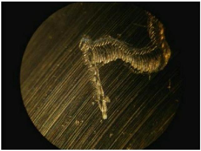 Avec une fraise pneumatique à graver le métal un défaut est gravé sur la piste de roulement d'un palier. Ce défaut est dégénérateur et va provoquer a terme la destruction de la pièce. On remonte le roulement et on introduit dans le palier la graisse XADO réparatrice pour le traitement des sous-ensembles usés jusqu'à 80%.